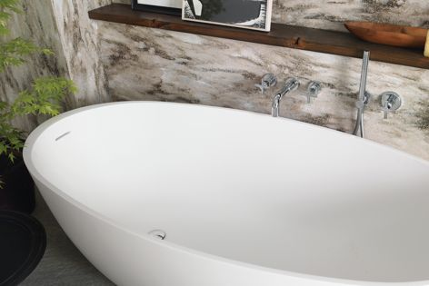 The oval freestanding Corian Delight bathtub delivers a sensory experience for a wellness oasis.