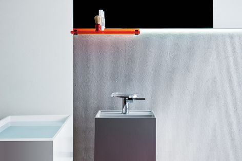 The Kartell by Laufen wall shelf and stool in tangerine orange, with a freestanding basin and bath.