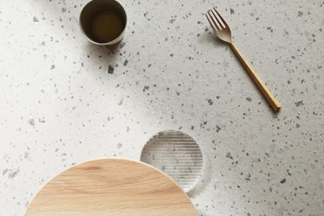 Laminex's Tinted Paper Terrazzo decor features grey and cream paper fragments dispersed across a pale, warm-grey base.