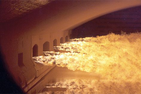 """Viridian's main furnace, with natural gas flames firing from one side over the molten glass """"lake."""""""